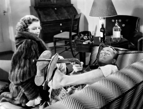 25th April 1934: Myrna Loy (1905 - 1993) and William Powell (1892 - 1984) play sleuthing couple Nick and Nora Charles in 'The Thin Man', directed by W S Van Dyke. In this scene Nick practises his aim using his feet to steady the muzzle of the gun.