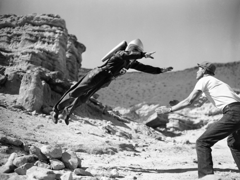"""Commando Cody, the Sky Marshal of the Universe,"" aka, George Wallace, appears to defy the laws of gravity, for a moment at least, as he lands in the arms of a prop man during production of the film "" Radar Men from the Moon,"" at Red Rock Canyon in the Mojave Desert, 80 miles northeast of Hollywood, Calif., Dec. 12, 1951. Gravity may be defied in some the new movie serials based on the fantasies science fiction, but what goes up still comes down, even if the film wont let you see it. (AP Photo)"